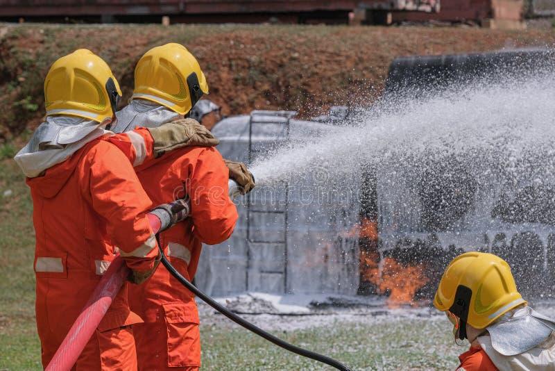 Les sapeurs-pompiers s'éteignent le feu avec la mousse chimique venant de la pompe à incendie par un long tuyau image libre de droits