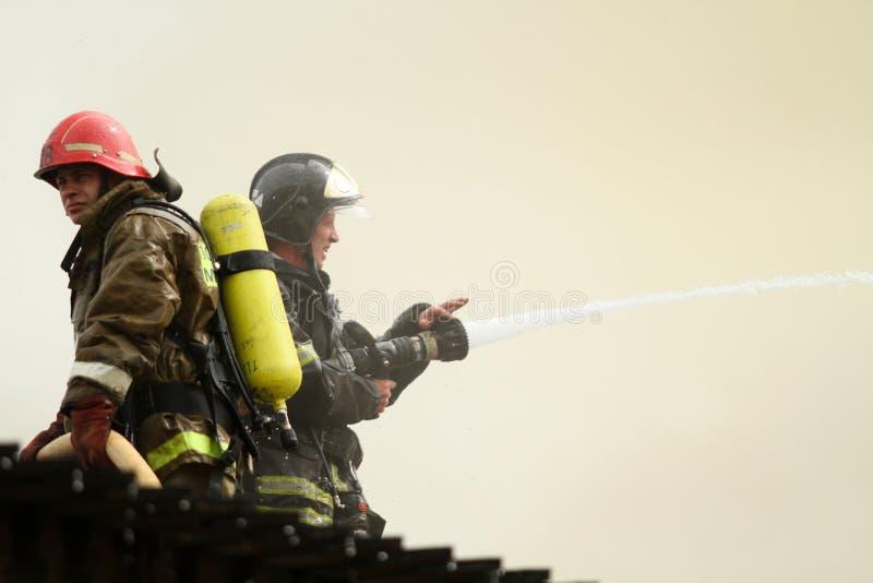 Les sapeurs-pompiers s'éteint un restaurant brûlant image libre de droits
