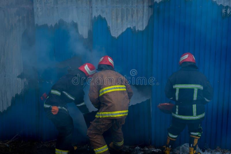 Les sapeurs-pompiers travaillent à un feu du bâtiment utilisant un outil de délivrance de coupeur en métal pendant un feu Le feu  image stock
