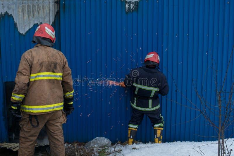 Les sapeurs-pompiers travaillent à un feu du bâtiment utilisant un outil de délivrance de coupeur en métal pendant un feu Le feu  photographie stock