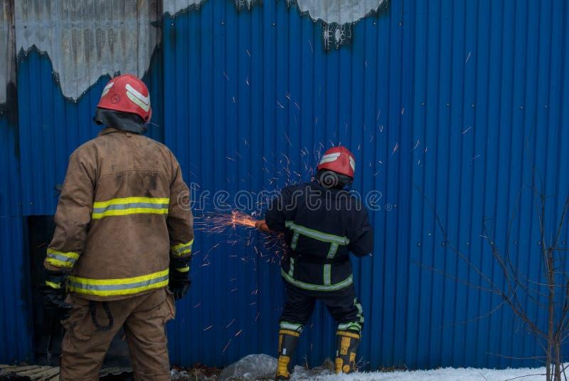 Les sapeurs-pompiers travaillent à un feu du bâtiment utilisant un outil de délivrance de coupeur en métal pendant un feu Le feu  images stock