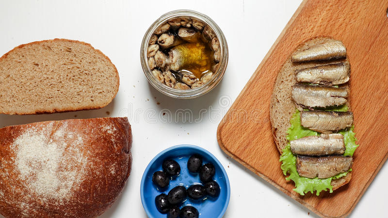Les sardines, esprots sur un morceau de pain noir avec de la laitue poussent des feuilles image libre de droits