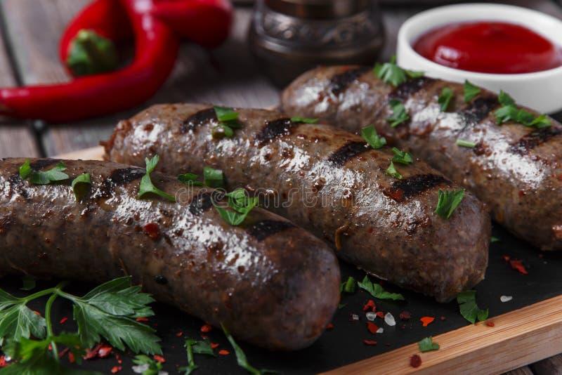 Les saucisses cuites faites maison ont fait frire sur un boeuf de gril photos libres de droits