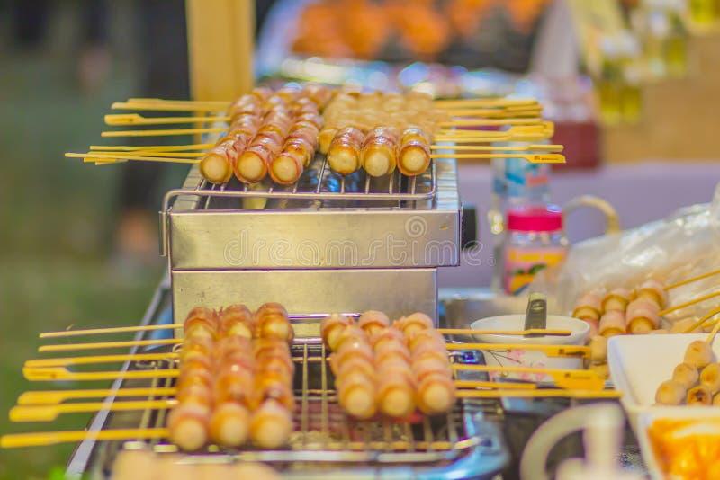 Les saucisses grillées de hot-dog enveloppées avec du jambon de lard couvre en vente sur le marché de nourriture de rue image libre de droits