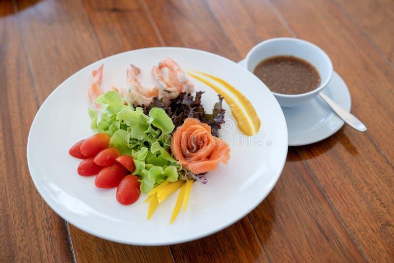 Les saumons crus de salade ont arrangé à coté à la forme rose et à la crevette bouillie dans le plat blanc sur la table en bois images libres de droits