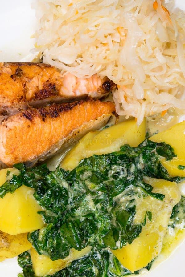 Les saumons cuits au four ont servi sur les épinards cuits, sauce à beurre, pommes de terre, salade fraîche photographie stock libre de droits