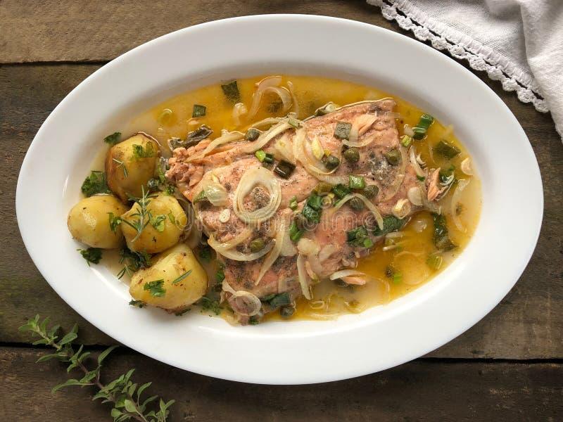 Les saumons gastronomes ont servi sur la table rustique ont rôti des saumons avec de la sauce à câpres images libres de droits