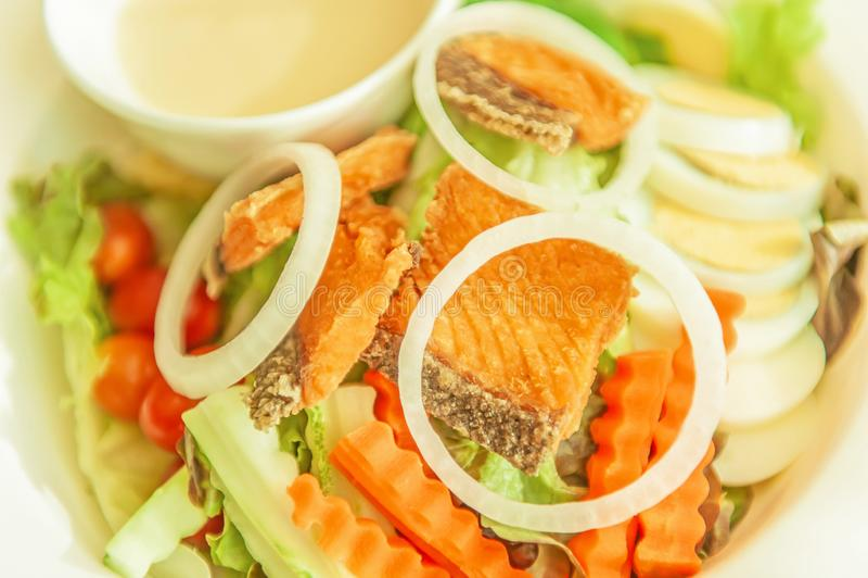 Les saumons grill?s avec de la salade, les anneaux de tranche d'oignon, la carotte, l'oeuf ? la coque et la sauce salade ont serv images stock