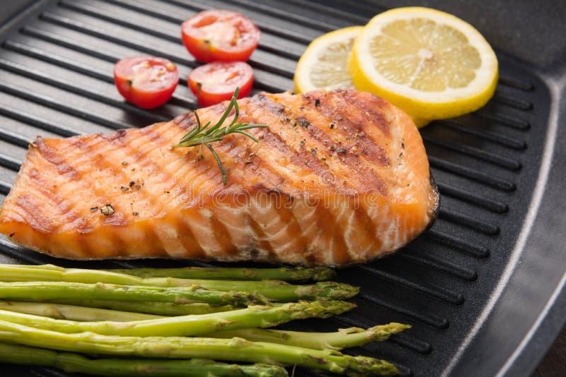 Les saumons grillés ont fait cuire le BBQ sur une casserole sur le fond en bois image stock