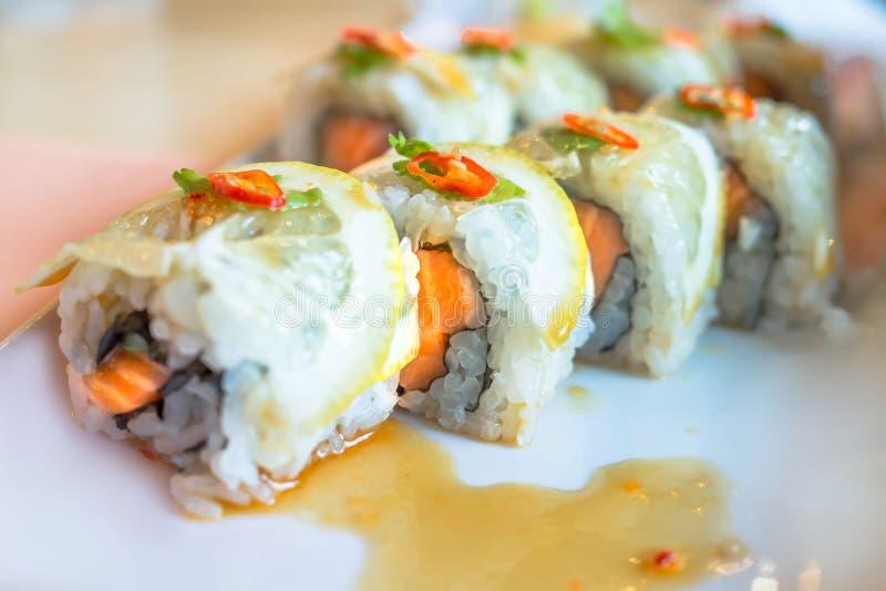 Les saumons roulent des sushi avec le foyer sélectif de citron avec le fond brouillé photos libres de droits