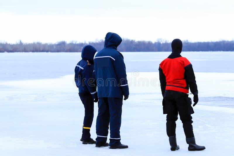 Les sauveteurs dans l'uniforme et le costume de plongée sont en service sur la rivière congelée pendant la pêche d'hiver et les m images stock