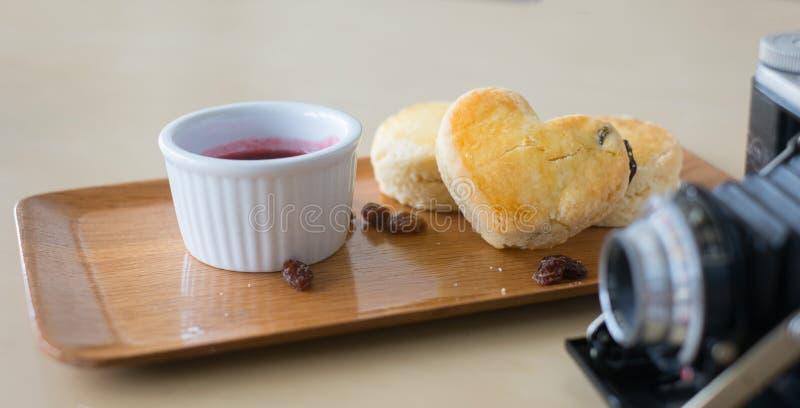 Les scones de rond et de coeur sur le dessus avec sèche des raisins secs avec de la confiture de framboise photos libres de droits