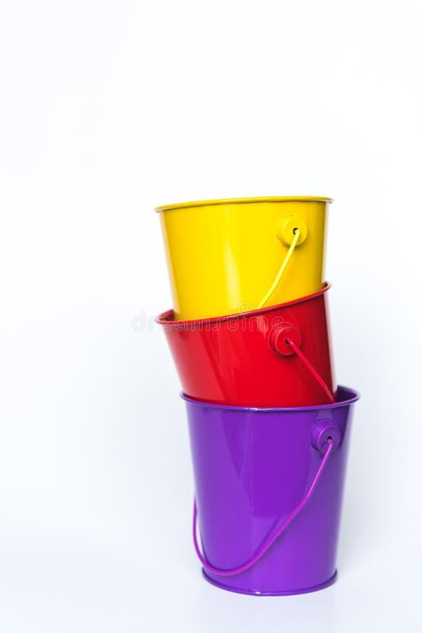 Les seaux en métal pourpres, rouges, et jaunes ont empilé ensemble le fond blanc solide image stock