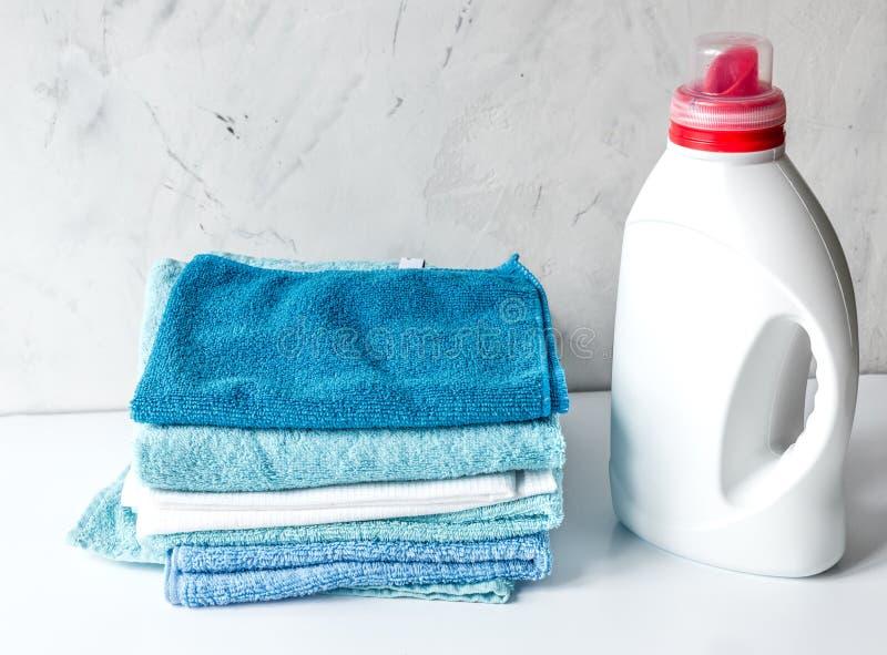 Les serviettes empilent dans l'ensemble de ménage sur la moquerie laudry de fond  photos stock