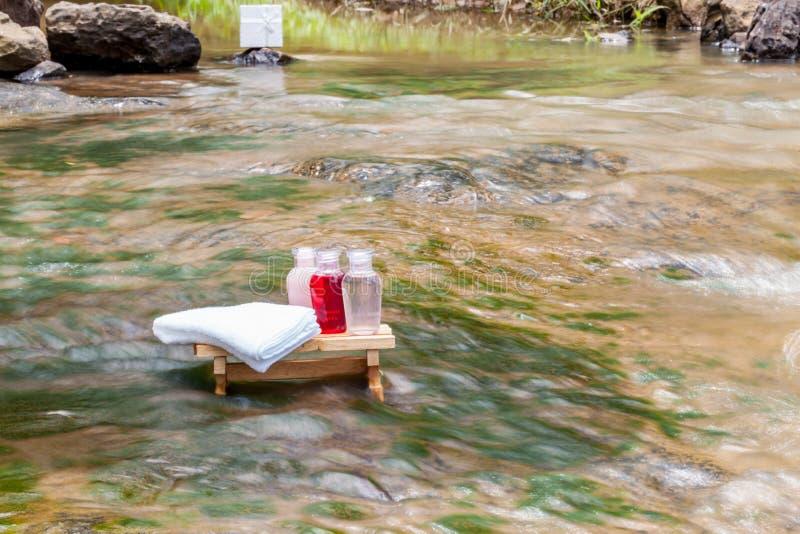 Les serviettes, les pétroles, le massage et la station thermale ont placé sur une table en bois à l'eau image stock