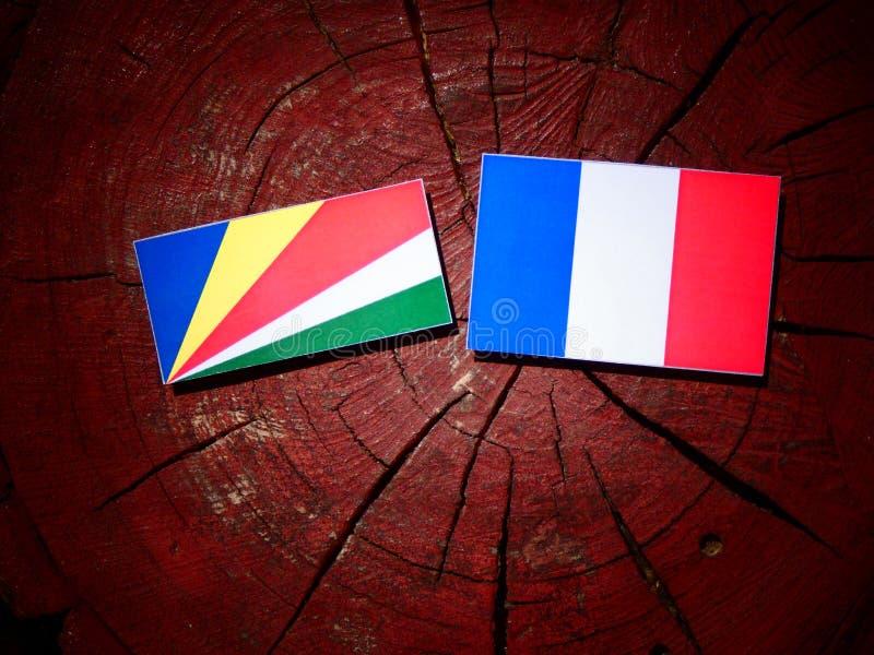 Les Seychelles diminuent avec le drapeau français sur un tronçon d'arbre d'isolement images stock
