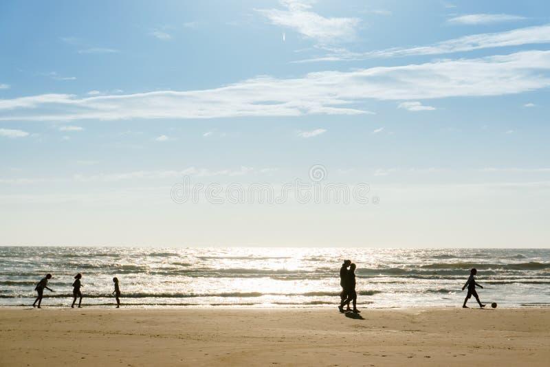 Les silhouettes d'un groupe de personnes marchant à la plage images libres de droits