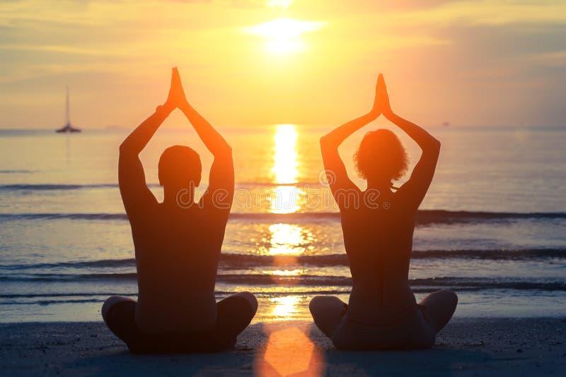 Les silhouettes de la méditation de l'homme et de femme sur le coucher du soleil échouent image libre de droits