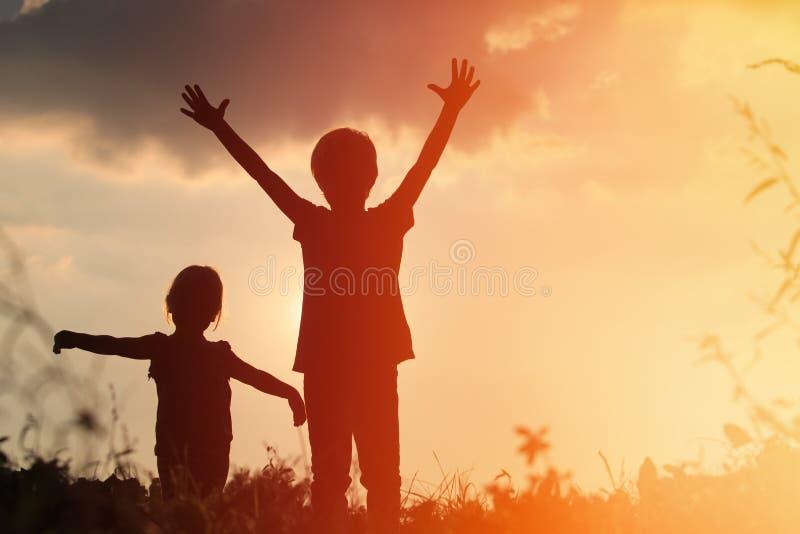Les silhouettes de petit garçon et de fille jouent au coucher du soleil image stock