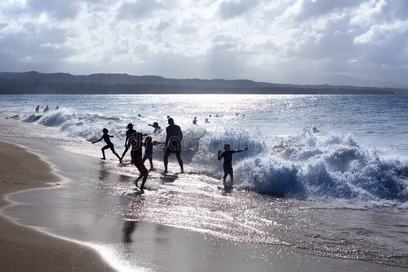 Les silhouettes des enfants et des personnes jouant sur la plage dans les vagues et l'eau éclabousse des vacances, mer bleue, lum image stock