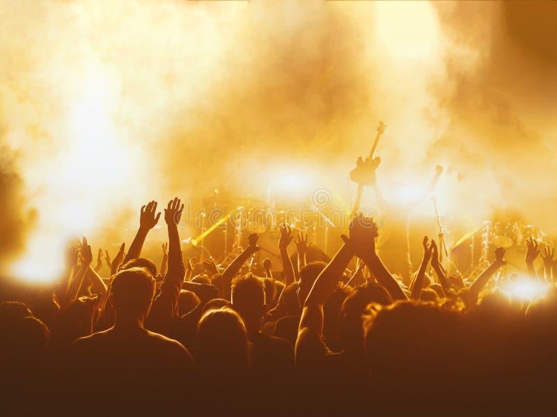 Les silhouettes du concert se serrent devant les lumières lumineuses d'étape photos libres de droits