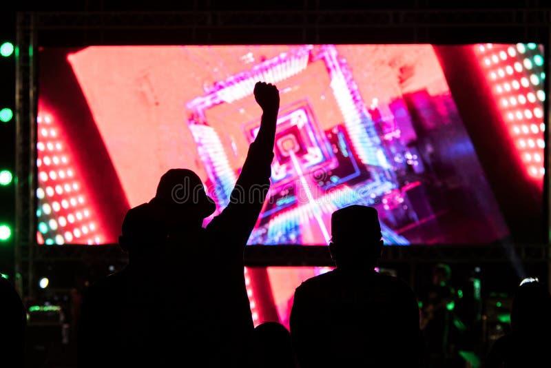Les silhouettes du concert se serrent devant les lumi?res lumineuses d'?tape photo stock