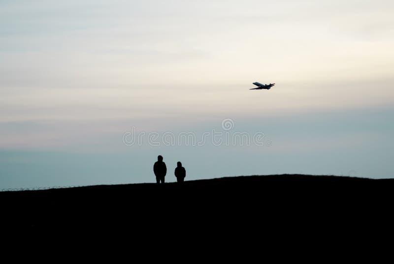 Les silhouettes du support de deux personnes sur une haute colline et observer une haute de vol d'avion dans le ciel photo libre de droits