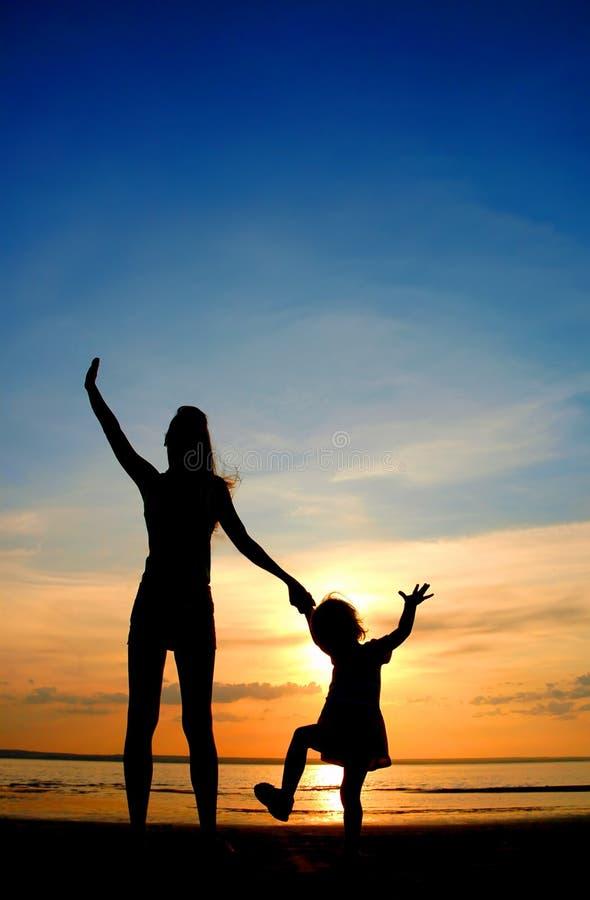 Les silhouettes enfantent et enfant sur le crépuscule photographie stock libre de droits