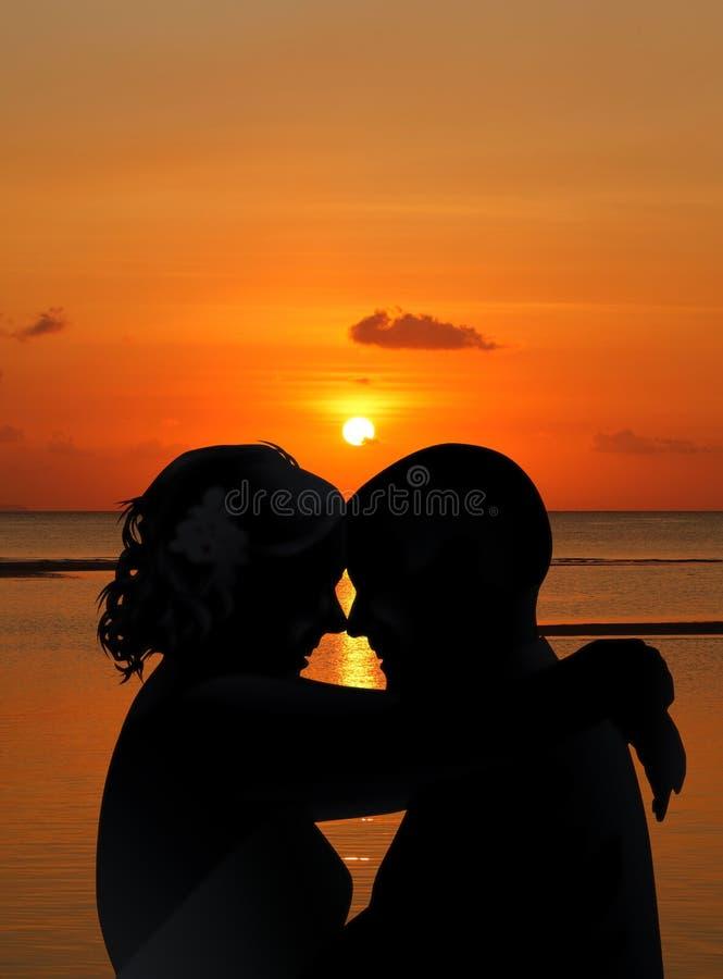 Les silhouettes s'accouplent sur la plage de coucher du soleil images stock