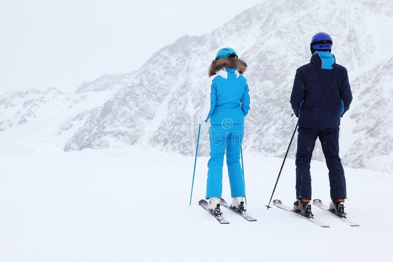 Les skieurs de femme et d'homme regardent la pente photographie stock