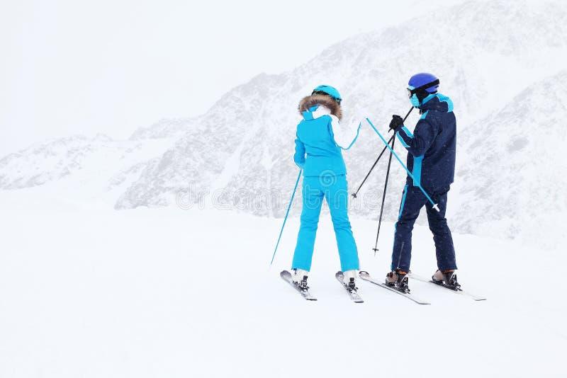 Les skieurs de femme et d'homme se préparent à la pente photo stock