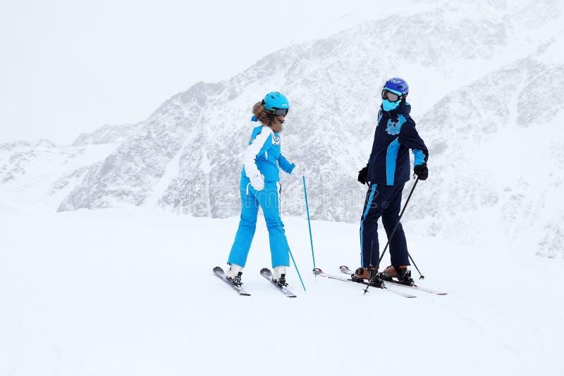 Les skieurs de femme et d'homme tournent en montagnes photos libres de droits