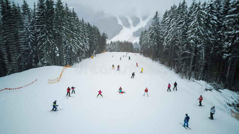 Les skieurs et les surfeurs descendent la pente dans une station de sports d'hiver Bukovel, Ukraine photographie stock libre de droits