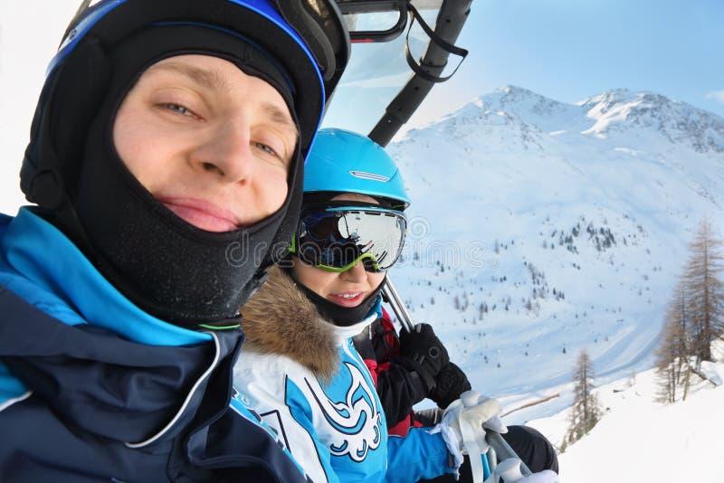 Les skieurs mâles et féminins conduisent sur le funiculaire photographie stock