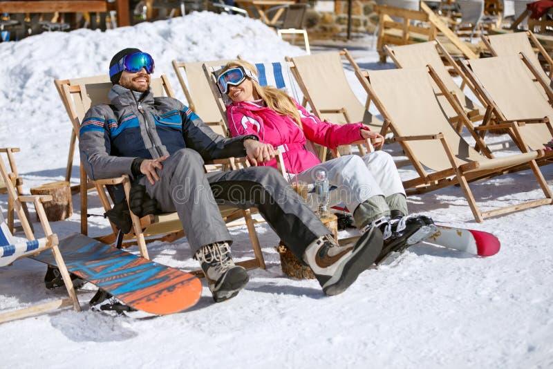 Les skieurs masculins et féminins apprécient dans des canapés du soleil image stock