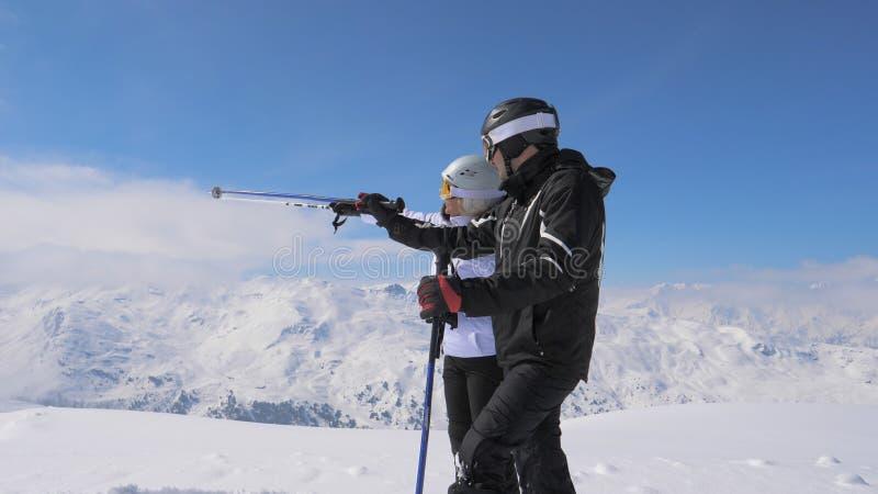 Les skieurs ont vu quelque chose intéressante dans la vallée de montagne et se montrent photo stock