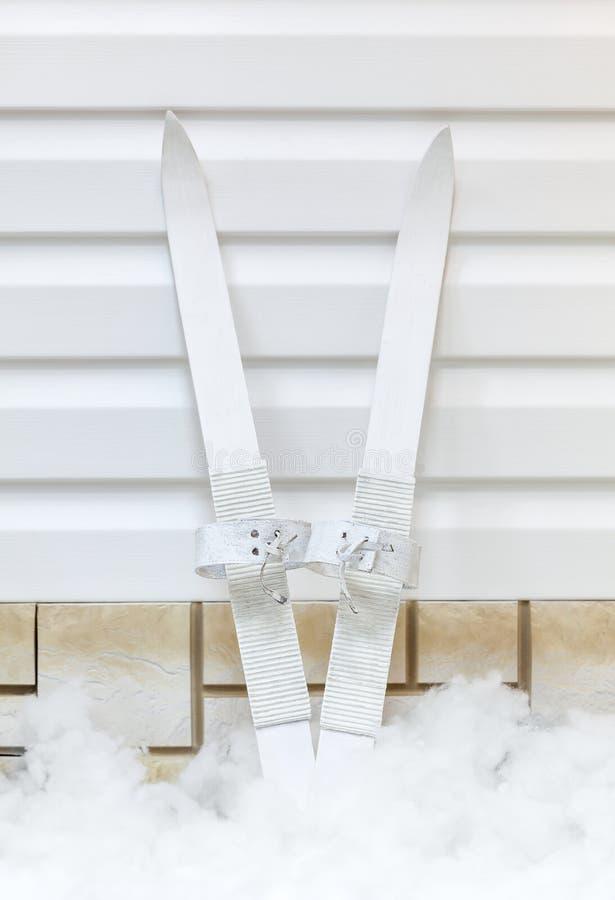 Les skis blancs de vintage du ` s d'enfants avec de vieilles ceintures ont lieu en hiver dans la neige autour de la maison le ski photo libre de droits
