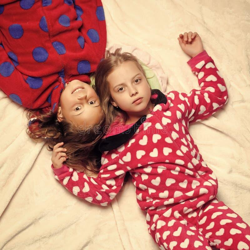 Les soeurs de fille dans des pyjamas se situent dans le lit, vue supérieure images stock