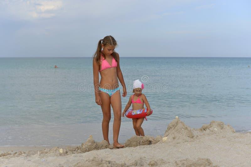Les soeurs de filles se tiennent dans des bikinis sur la plage sablonneuse un jour d'été photos libres de droits
