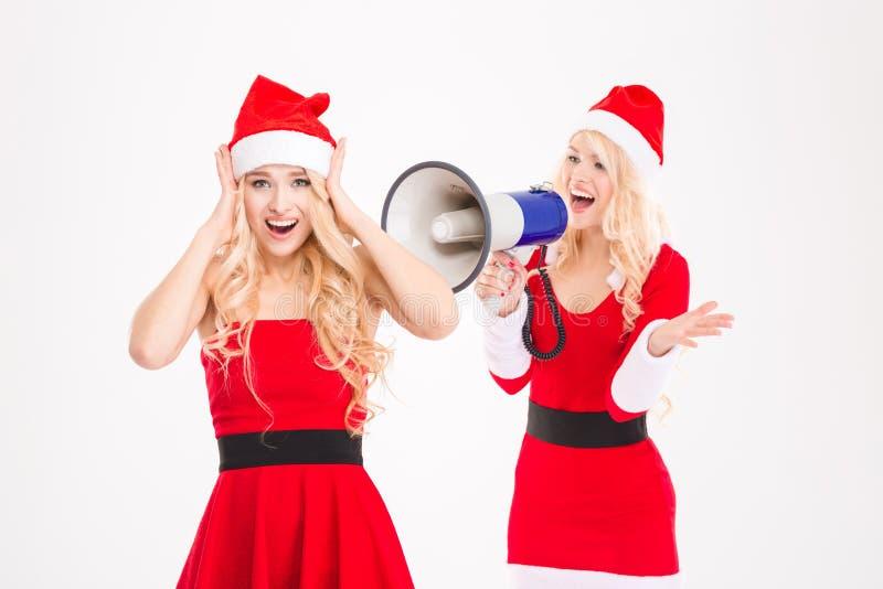 Les soeurs jumelle dans des costumes rouges du père noël criant sur le mégaphone photographie stock libre de droits