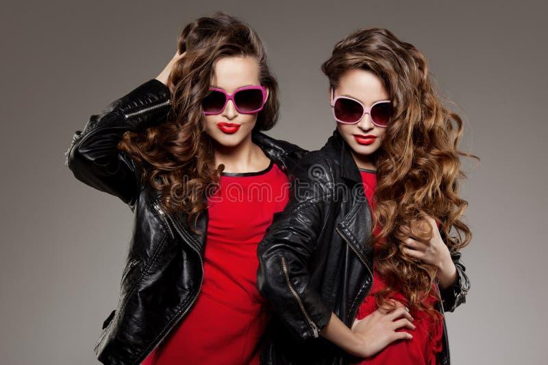 Les soeurs jumelle en verres de soleil de hippie riant deux mannequins image stock