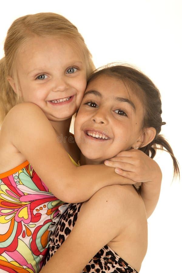 Les soeurs mignonnes utilisant des maillots de bain s'étreignant aimant sourit images libres de droits