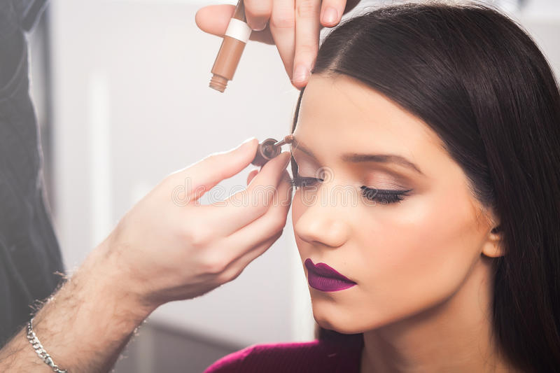Les sourcils masculins de Colors d'artiste de maquillage à la fille de brune dans un salon beaty, se ferment  photos libres de droits