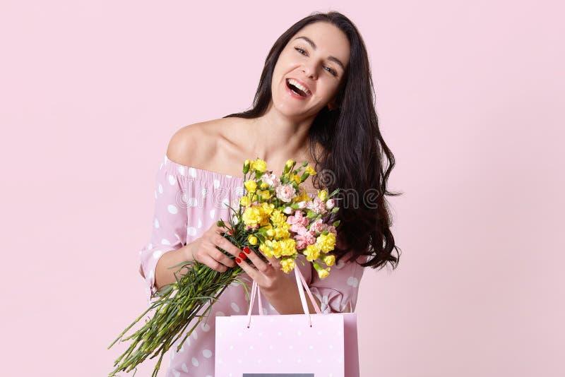 Les sourires d'une chevelure foncés joyeux de jeune dame heureusement, habillé dans des vêtements élégants, heureux de recevoir l photo stock