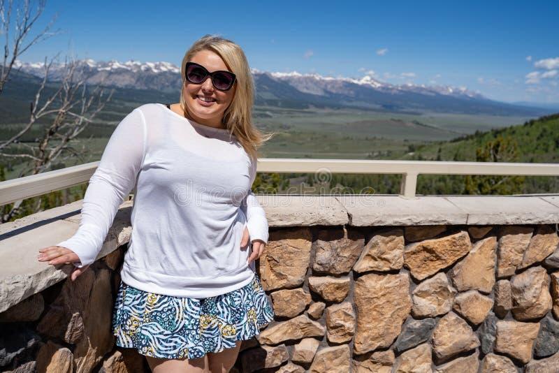 Les sourires et les poses blonds adorables de femme pour une photo de touristes au sommet de galène donnent sur dans les montagne photos stock