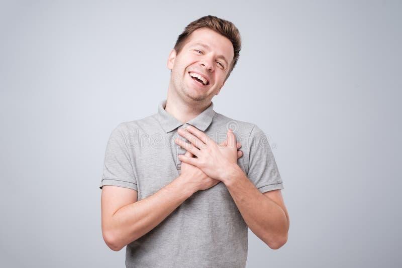 Les sourires gais d'homme heureusement, garde des mains sur heureux masculin heureux par coffre de recevoir le compliment de la f photos stock