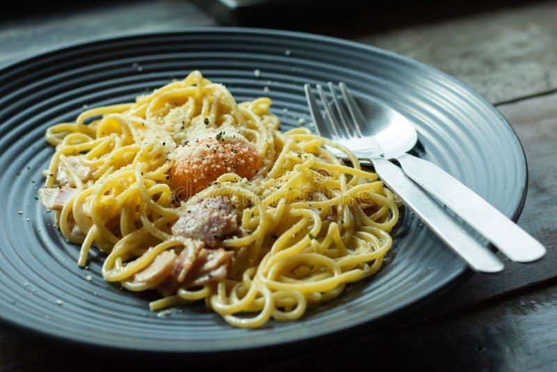 Les spaghetti, fromage frit d'un plat noir sur la table image libre de droits