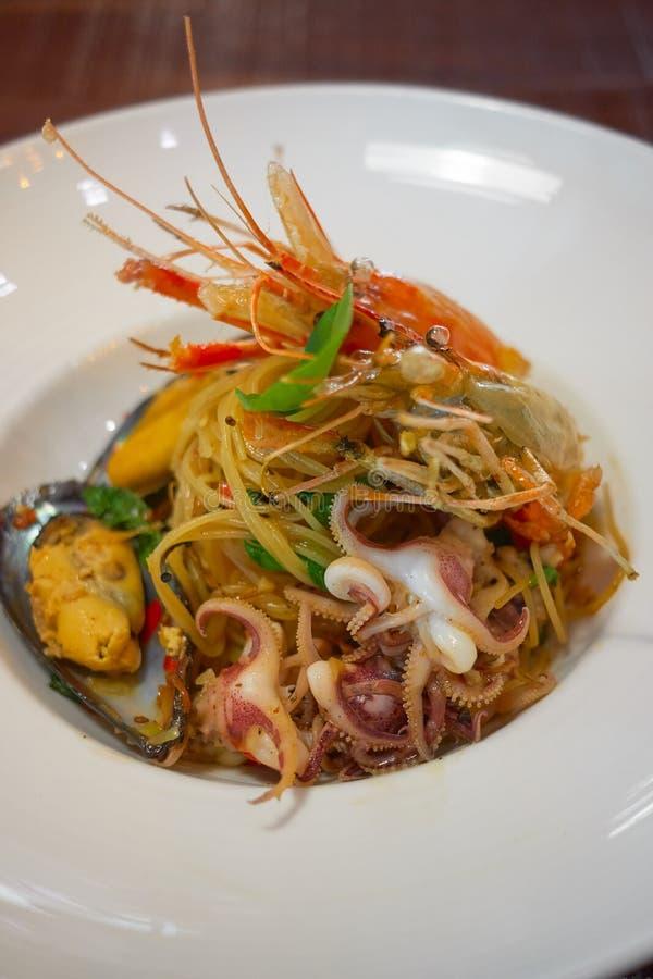 Les spaghetti ?pic?s de fruits de mer remuent la protection frite Cha ont roul? dans la fourchette sur le plat blanc du restauran images stock