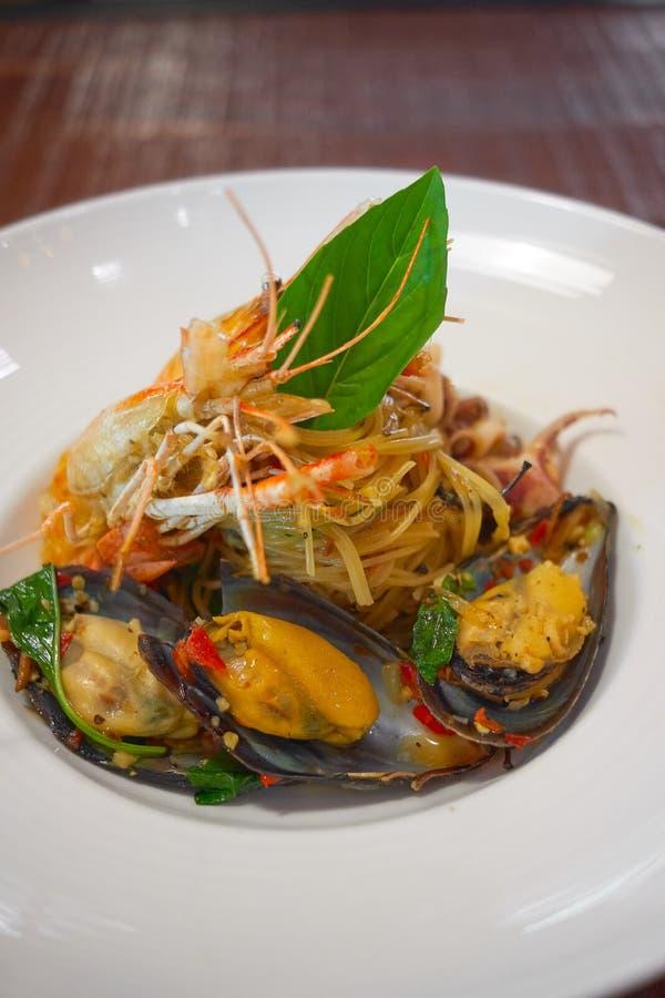 Les spaghetti ?pic?s de fruits de mer remuent la protection frite Cha ont roul? dans la fourchette sur le plat blanc du restauran photographie stock libre de droits