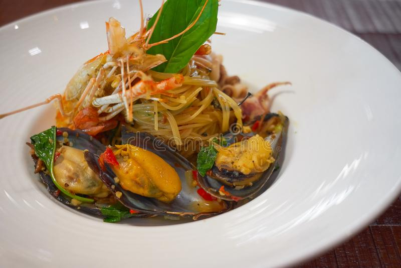 Les spaghetti ?pic?s de fruits de mer remuent la protection frite Cha ont roul? dans la fourchette sur le plat blanc du restauran image stock